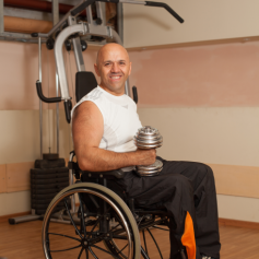 man in wheelchair pumping iron in the gym with a dumbbell