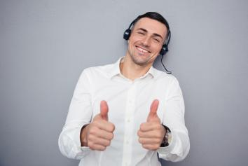 Man on headset giving 2 thumbs up.